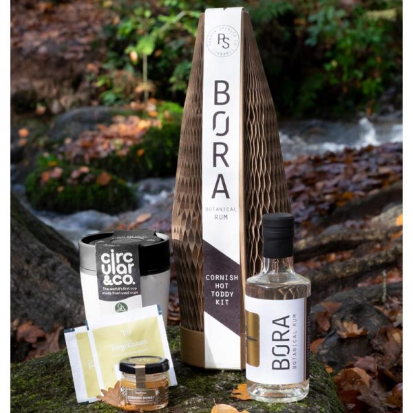 Hot toddy giftset sitting on rocks showing bottle of rum, cup, honey and teabag