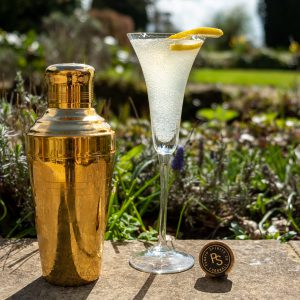 BORA 75 cocktail in flute glass alongside a gold tumbler